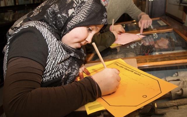 Young refufee takes part in activity at the Pitt Rivers Museum
