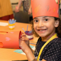 Young girl making a paper crown