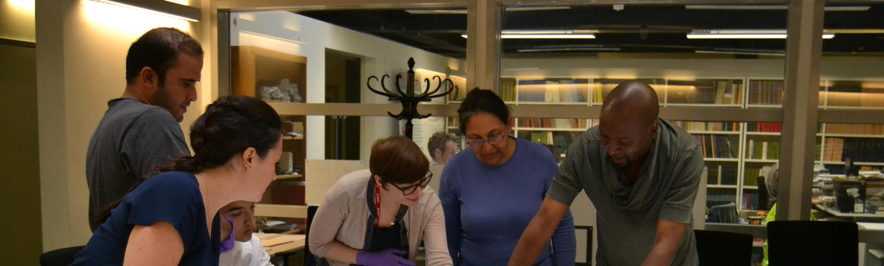 2 collections officer abigael flack shows volunteers a textile from syria