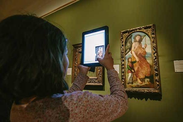 Young person examining art work using iPad application in the Ashmolean Museum