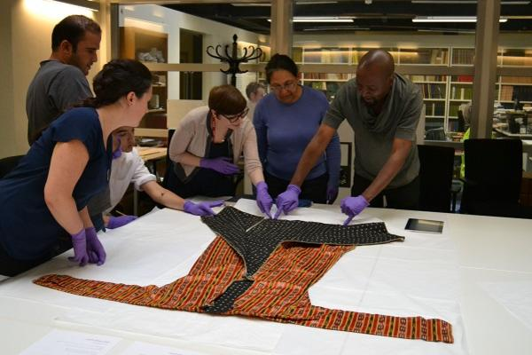 Collections Officer Abigael Flack shows Multaka volunteers a textile from Syria. (c) Pitt Rivers Museum