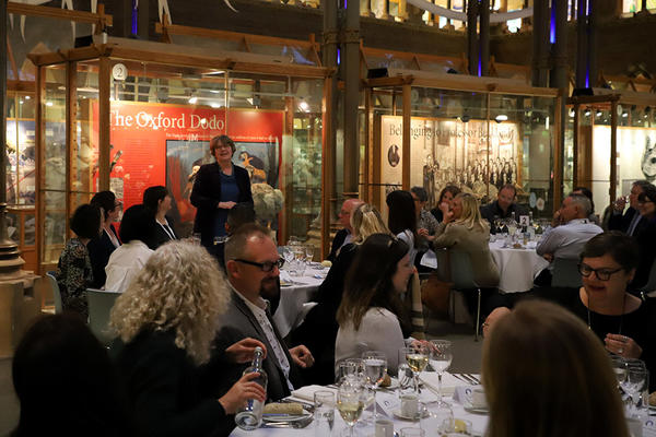Adults sat down at tables for dinner in a museum