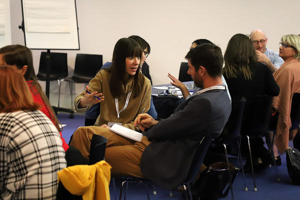Adults discussing in pairs in a seminar room