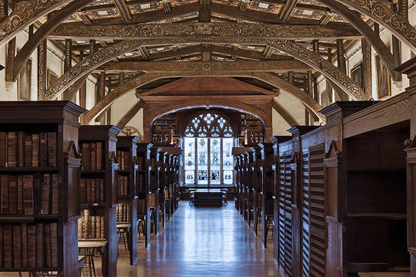 Long room with rows of old book shelves and wooden beams above