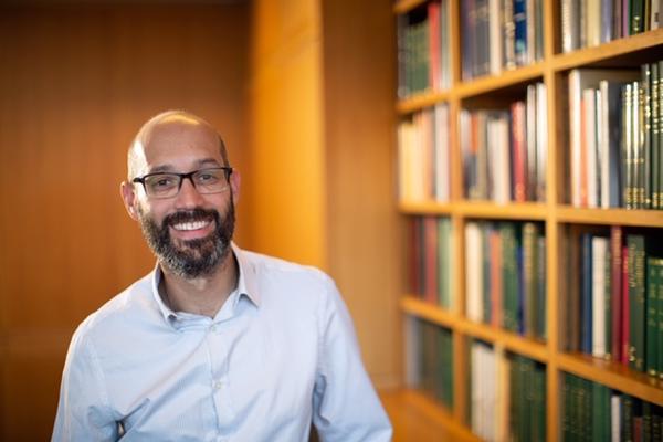 Man smiling stood beside bookcase