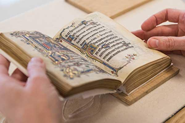Person handling book of prayers from Bodleian Libraries' Special Collections