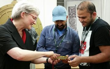 Volunteers Tammam and Abdullah examine an astrolabe with MHS director Silke Ackermann