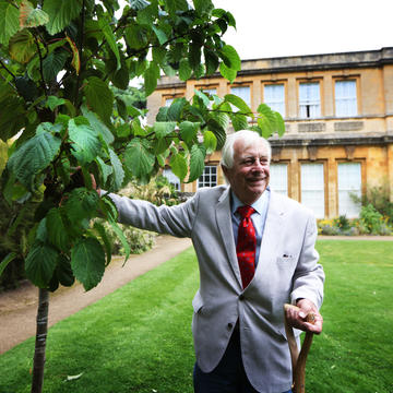 Chancellor Chris Patten stands beside a tree he has just planted