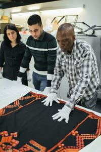 Volunteers Nav, Hussein and Niran lay out a dress from Saraqib